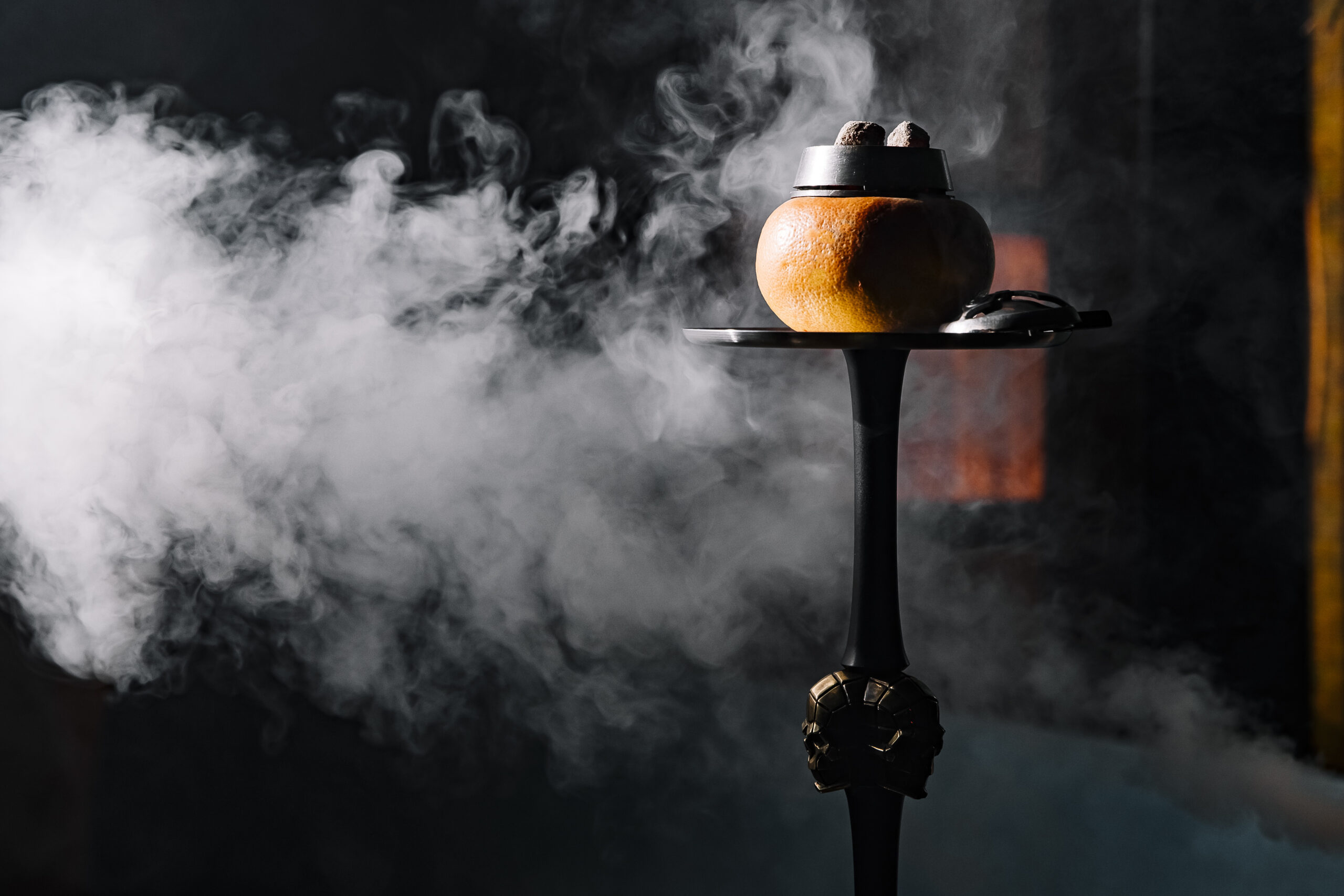 side view of fruit shisha bowl with melon and fume on dark background